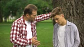 понимание : Dad scolding his son for bad behavior, education process, fathers and children Стоковые видеозаписи