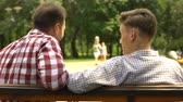 fete des peres : Bearded father communicating with teenage son, sitting on bench in park, trust Vidéos Libres De Droits