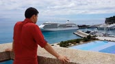 miljonair : Businessman in casual clothes observing his yacht in port, view from terrace