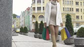 anyaság : Beautiful mother-to-be walking city street shopping bags, childbirth preparation