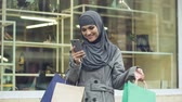 stile etnico : Happy Arabic lady using online shopping app for searching discounts.