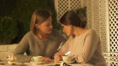 divorce : Young lady comforting and hugging her upset friend, having coffee on terrace