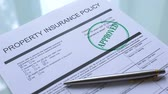 odszkodowanie : Approved property insurance policy, hand stamping seal on official paper closeup Wideo