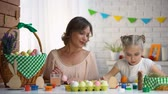 home painting : Daughter and mother painting Easter eggs with colorful dye preparing for fest