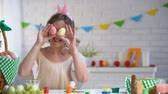 piada : Smiling woman having fun holding colorful Easter eggs near her eyes.