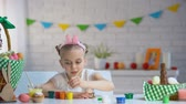 girl left : Left handed girl brushing Easter eggs with paint, creativity, childrens hobby Stock Footage
