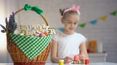 namalovaný : Happy Easter sign on basket, cute girl painting eggs sitting at table, holiday