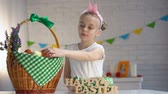 egg painted : Female kid counting colored eggs and putting in basket, happy Easter greeting Stock Footage