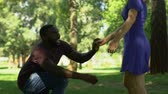 marry : Afro-american man making proposal to girlfriend while they walking in park
