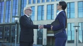 買収 : Two business people shaking hands outdoors, merger and acquisition agreement
