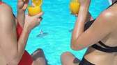 suntan : Women with legs in pool clinking and drinking cocktails, summertime leisure
