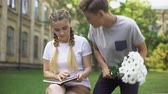 влюбленный : Teen reading book when young man presenting field flowers, first love, flirt