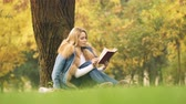 uczenie się : Pretty woman reading interesting book, sitting under tree, spending leisure time