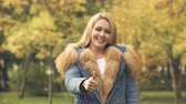 refah : Happy woman smiling and showing thumbs up in autumn park, social insurance