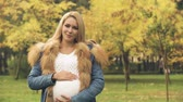 várakozás : Happy pregnant woman looking at camera, maternity clinic, reproductive system