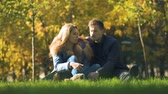 téma : Serious couple speaking in autumn park sitting on plaid, discussing relationship