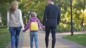 Parents and daughter going to school, conscious parenthood, care, back view 動画素材