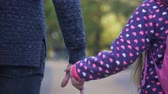 anyaság : Single father and daughter holding hands and walking forward together, autumn
