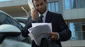 Business person talking on phone near car, solving financial issues of company 動画素材