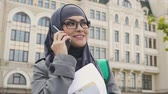 graduação : Muslim woman talking on phone, waiting near college for classes, study abroad