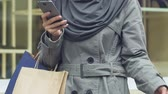 muslimah : Muslim woman carrying purchases, using app on phone to call taxi after shopping