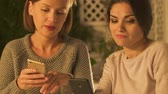 ököl : Women looking at social network page of their friends, discussing rumors closeup