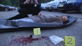 investigare : Bloody female corpse and drugs lying on asphalt, police working on crime scene