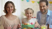 farba : Friendly family posing at camera with basket of brightly colored Easter eggs