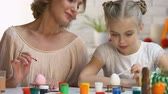 hard boiled eggs : Mother watching daughter painting Easter egg for first time, family traditions Stock Footage
