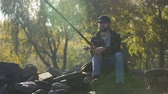 шестерня : Fisherman spinning fishing reel, sitting on stones, enjoying leisure, autumn