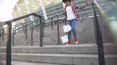 žebřík : Young african american woman running down stairs, student hurrying to classes