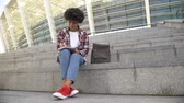 fare i compiti : Cute curly haired female student doing homework, sitting on stairs near arena Filmati Stock