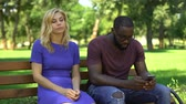 etnický : African american man playing cellphone on date in park, ignoring sad girlfriend