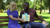receber : Afro-American man reading book in park, getting surprised female friend present