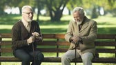 canne : Two old men relaxing and having fun in park of nursing home, happy memories