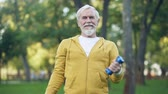 hetvenes évek : Handsome aged man doing arm exercises with dumbbells in park, leisure activity