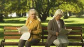convince : Two senior offended female friends reading newspapers, sitting on bench in park Stock Footage