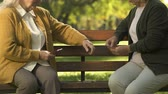 card game : Two old women enjoying cards playing on bench in park, elderly friends leisure Stock Footage