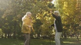 aposentar : Two elder friends dancing and having fun in autumn park, active lifestyle, joy