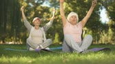 meditare : Elder women sitting in lotus position and meditating doing yoga in park, energy