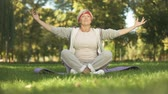 meditate : Middle age woman deeply breathing and meditating sitting in lotus position Stock Footage
