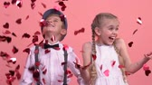 Cute children enjoying rain from bright heart-shaped confetti, St Valentines day 動画素材