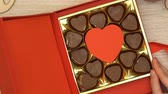simbolismo : Woman open gift box with heart-shaped chocolate candies aphrodisiac, top view