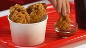 不健康な食事 : Womans hand dipping fatty crispy drumstick into tomato sauce, fast food meal
