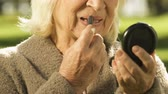 pension : Elderly lady applying lipstick, beauty care for old people, anti-aging cosmetics Stock Footage