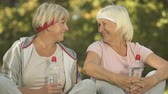 pensão : Female active pensioners looking in camera, sitting in park with water bottles
