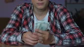 man spend money : Teenage boy in plaid shirt counting money, sitting home table, financial savings Stock Footage