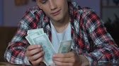 man spend money : Handsome teenager counting dollar bills, sitting at table, dreaming purchase Stock Footage