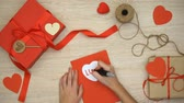 érez : Hand writing love word on greeting card lying on table with craft gift boxes