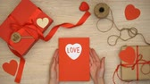 parabéns : Hands holding Valentines greeting card with love word, gift boxes on background